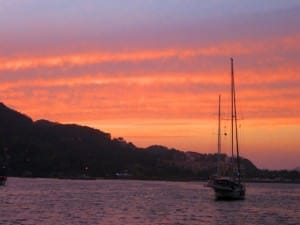 sunset over water and sailboat