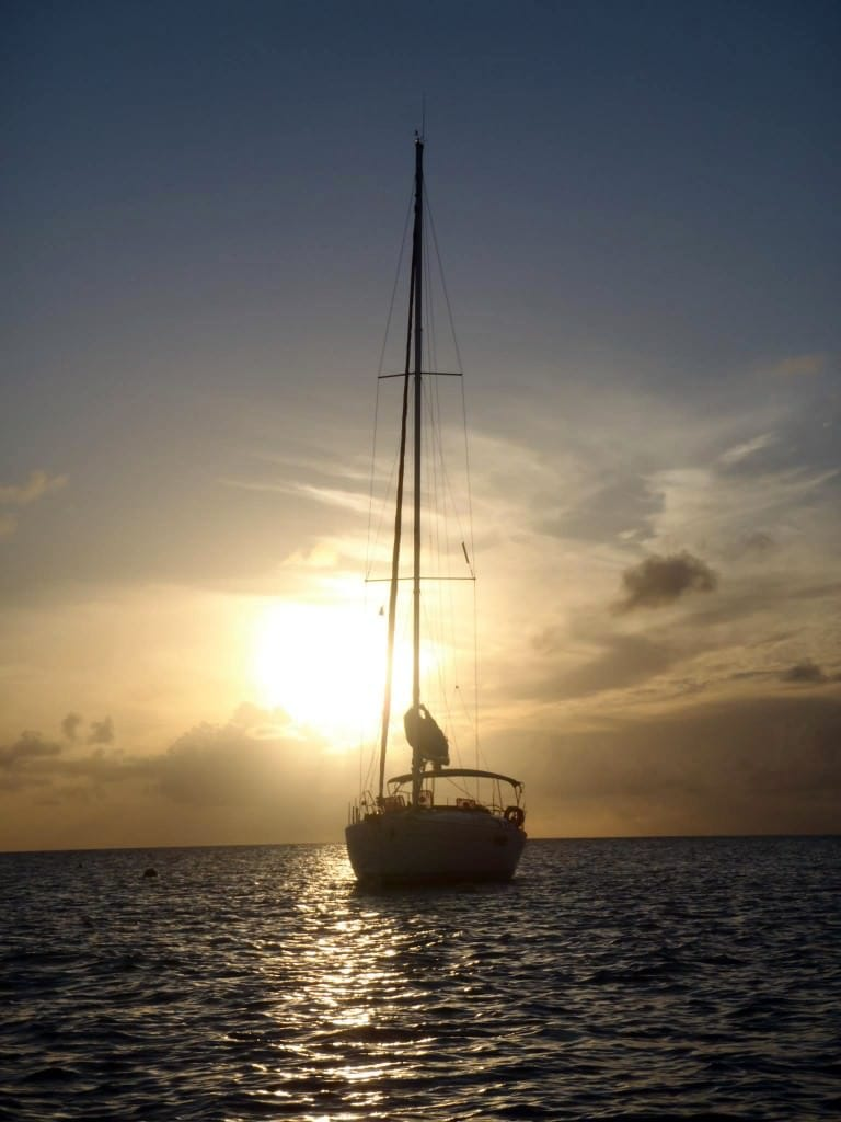 sun behind sailboat at anchor